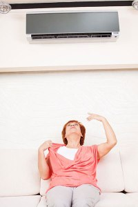 woman-sitting-under-air-conditioner