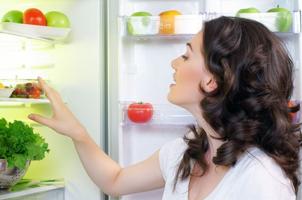 Woman-Looking-at-open-refrigerator-full-of-food