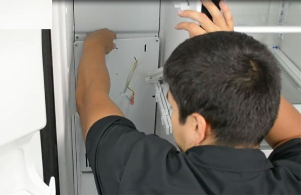 A man removes the back freezer panel inside a refrigerator freezer in order to work on the defrost system.